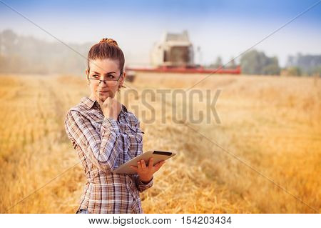 Nice Farmer Woman In Glasses With Hair Tied In A Ponytail Standing With Tablet And Thinking In Wheat