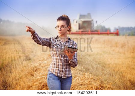 Agronomist Girl In Glasses With Tablet Controls The Harvesting In Wheat Field