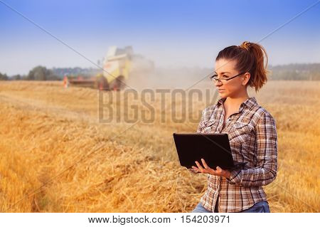 Farmer Girl In Glasses With Hair Tied In A Ponytail Controls The Harvesting