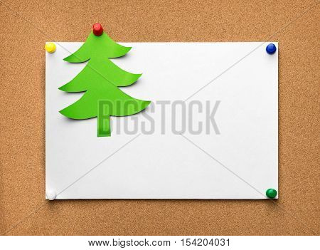 Christmas tree made of green paper and blank sheet on the cork board