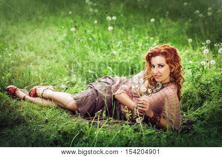 Hippie Girl With Red Curling Hairs Lying On The Green Grass With Dandelion And Smiling. Horizontal.