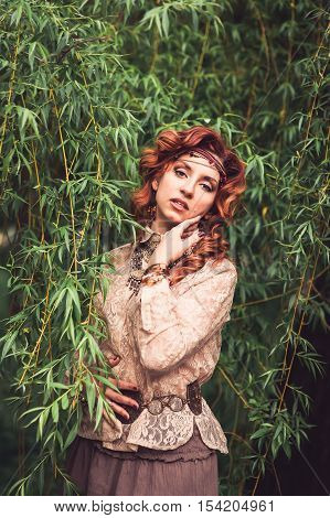 Hippie Girl Standing Under The Willow Tree Ruffling Long Red Curling Hairs. Decorations In Favorable