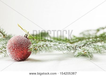 Red christmas or new year ornament on snow with pine tree branch.