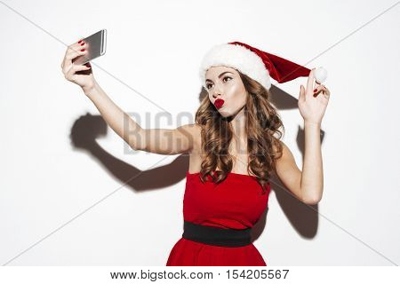 Attractive playful young woman in santa claus costume taking selfie with cell phone