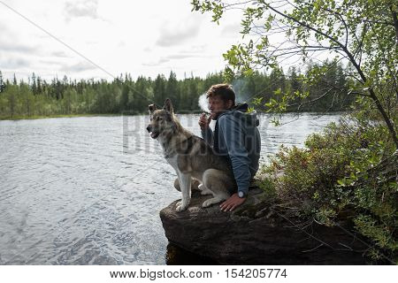 Man with cigarette and his dog are sitting on the stone near of lake and looking into the distance