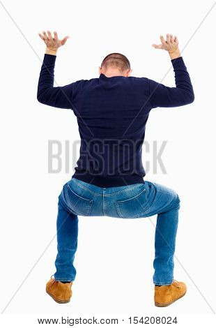 back view. man  protects hands from what is falling from above. Man holding a heavy load backside view person.  Isolated over white background. A guy in a black sweater, sat down under the weight load