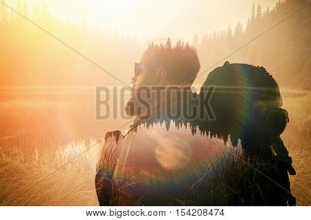 Portrait of stylish bearded man with glasses and tourism backpack. Double exposure view on the beautiful mountain lake. Wide sunset effect.