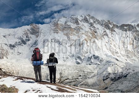 View of Mount Annapurna with two climbers round Annapurna circuit trekking trail Nepal