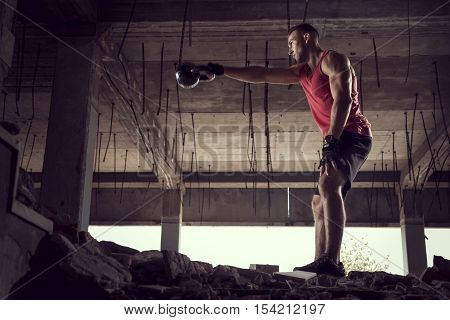 Side view of a young muscular athletic built man working out lifting a kettlebell weight in an abandoned ruined building