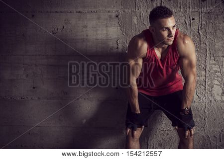 Muscular young athletic built sportsman leaning against a concrete wall of an abandoned building taking a break