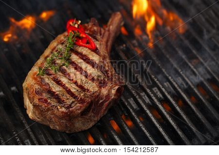 food meat - beef steak on bbq barbecue grill with flame. Shallow dof.