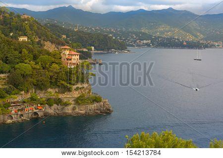 Windy wavy road along Portofino cove, street cut into cliff at Portofino port, Italian fishing village, Genoa province, Italy