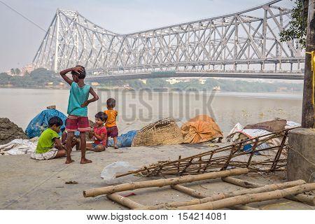 KOLKATA, INDIA - OCTOBER 8, 2016: Street kids play at the bank of the river Ganges at Mallick ghat close to the Howrah bridge, Kolkata, India.