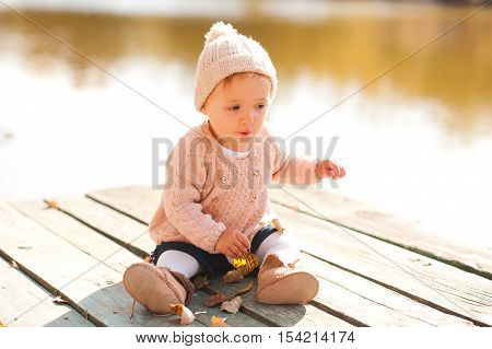 Cute baby girl 1-2 year old sitting on wooden pier playing with autumn leaves outdoors. Childhood.