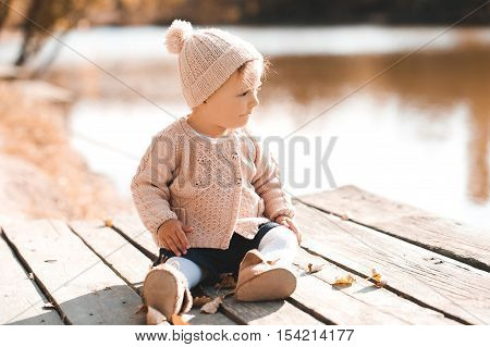 Stylish baby girl 1-2 year old wearing knitted sweater and hat sitting on wooden pier outdoors.Looking away. Childhood. Autumn season.