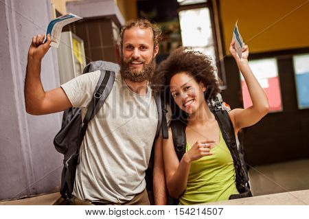 Happy And Euphoric Couple Of Backpacker Tourists Show Tickets For Their Trip