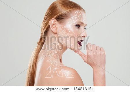 Nude woman with body art. Stands sideways. close up