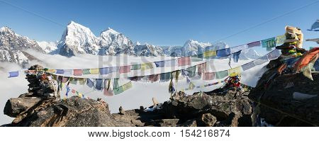 view from Gokyo Ri to Arakam Tse Cholatse Tabuche Peak Thamserku and Kangtega with prayer flags - trek to Everest base camp - Nepal