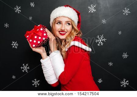 Portrait of cheeful charming young woman in santa claus hat holding gift box over black background