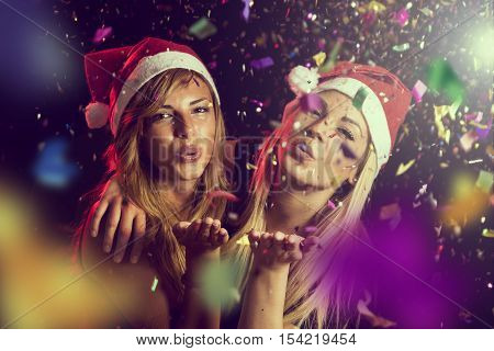 Two beautiful young girls having fun at New Year's Eve party sending kisses