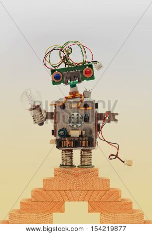 Toy robot on top of the wooden steps, vintage staircase. Kindly character with electrical wire hairstyle. handmade mechanism, funny head, colored blue red eyes, light bulb in hand.