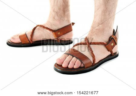 Brown leather sandals on man's feet isolated on white