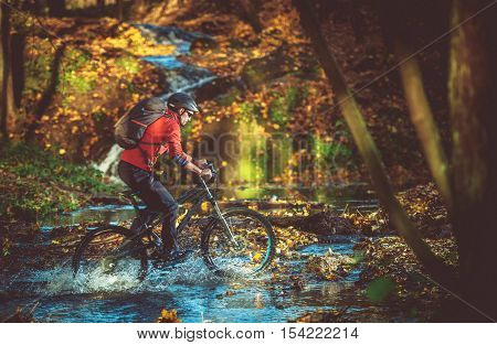 Bike RIde in the Scenic Fall Foliage Forest. Forest River Crossing. Caucasian Mountain Biker.