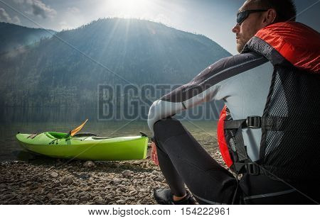 Caucasian Kayaker in the Sun. Kayaker Enjoying Scenic View While Seating on the Lake Shore.