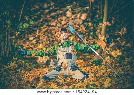 Gardener Welcome Fall Season Between Flying Colorful Leaves. Autumn Season Landscaping Concept. Happy Gardener with Rake.