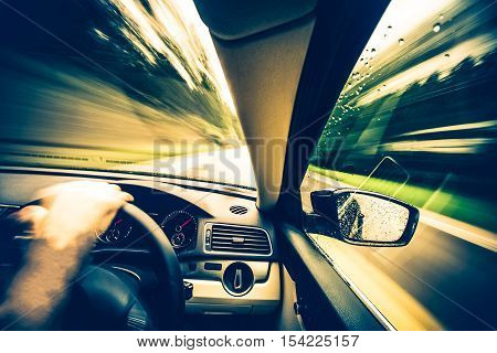 Left Side Driving Concept. Speeding Car with Right Side Steering Wheel on the Forest Road.