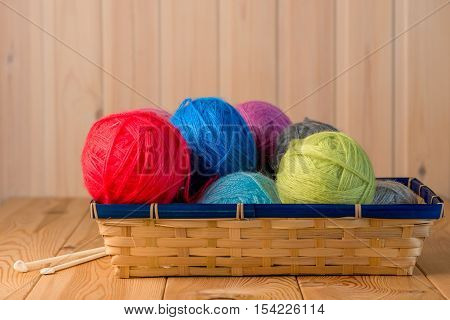 Straw Basket Packed Full Of Woolen Threads On A Wooden Table