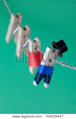 Creative design peg characters and clothesline. Man in suit, woman red dress. wooden clothespins on green background. Macro view