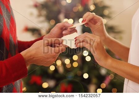 Cuple sharing Christmas wafer in traditional Polish way