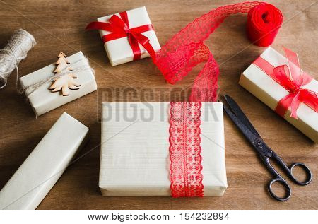 Packing Christmas Gifts. Top View of Festive Boxes in Brown Paper Decorated with Red Bow Ribbon Christmas Tree and Jute on Wooden Table. Selective Focus. Copy Space.