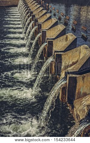 Water cascading through concrete overflow weir across the Dambovita river in central Bucharest Romania. City clean water supply management. Renewable energy.