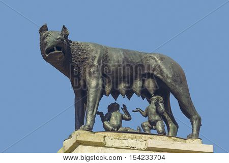 Bucharest Romania - April 14 2014: Bronze sculpture replica of Capitoline Wolf (Lupa Capitolina) depicting a she-wolf suckling twin human infants Romulus and Remus the legendary founders of Rome.