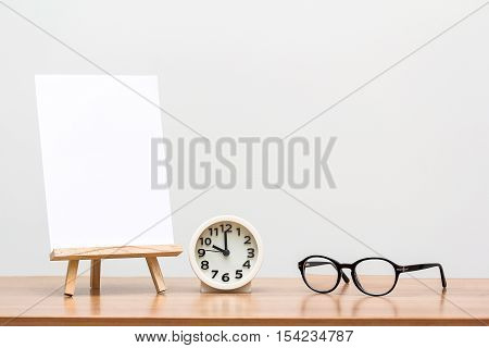 wooden easel with blank canvas round clock and glasses on table