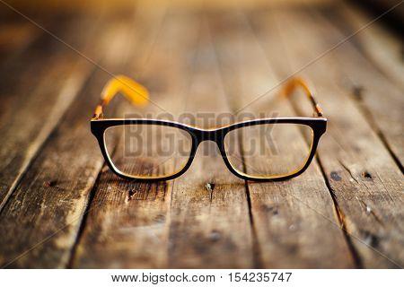 Glasses  Lie On The Dark Wooden Table.   Black Orange  Glasses