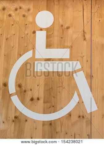 Handicap Wheelchair WC Sign: White Restroom Symbol on Wooden Background