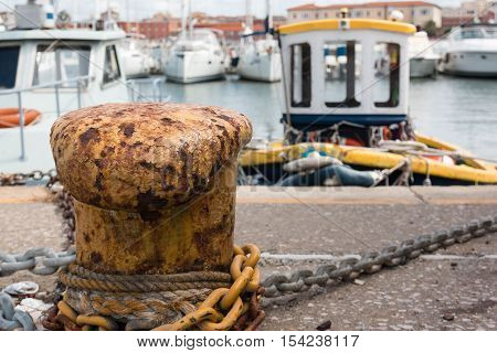 Closeup of Rope and Metal Cable Tied to Yellow Rusted Bollard Fishing Boats in Background