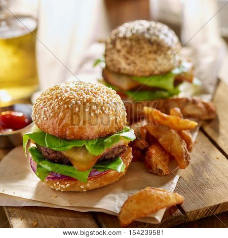 burgers and seasoned wedge fries with ketchup and beer