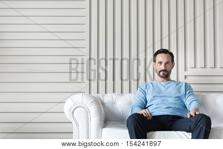 Time to relax. Confident good looking nice man sitting on the couch and putting his hands on the legs while having a rest