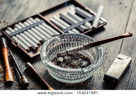Glass Ashtray With Thin Wooden Pipes, Cigarettes And Lighter Around