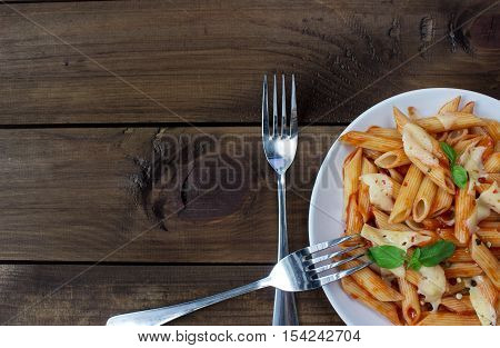penne pasta in tomato souce on old wooden table. with space for text. view from above