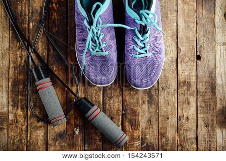 Set For Sports On Wooden Table, Closeup. Rope And Sneakers On T