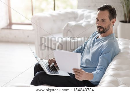 Work with documents. Nice hard working cheerful man holding a laptop on his knees and typing something while looking at the documents