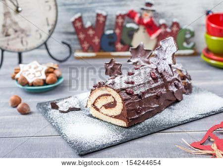 Cakes Christmas Log Bush de Noel home kitchen on New Year decorated wooden background