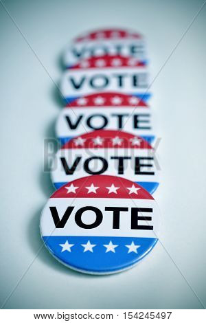 some aligned badges with the word vote written in it, for the United States election, with a slight vignette added