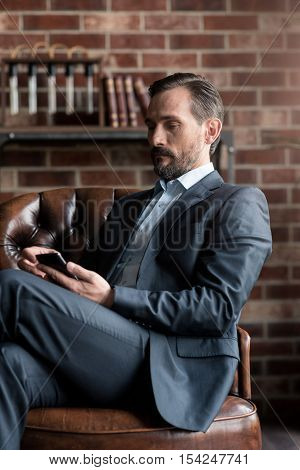Device for communication and interaction. Nice serious good looking man sitting in the armchair and holding his cell phone while using it