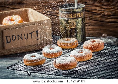 Icing sugar falling on fresh donuts on wooden table